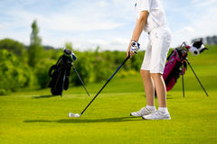 Kids playing golf. Legs of boy golfer with golf club at golf course at summer day Stock Image