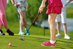 Kids playing golf. Legs of kids playing golf and hitting by putter on green royalty free stock photography