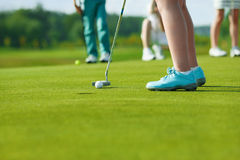 Kids playing golf. Legs of kids playing golf and hitting by putter on green Stock Photography