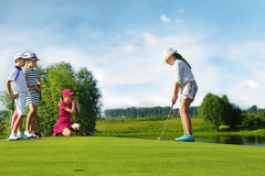 Kids playing golf. By putter on green Royalty Free Stock Images