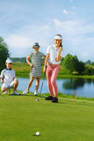 Kids playing golf. By putter on green Royalty Free Stock Photos