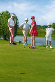 Kids playing golf. By putter on green Royalty Free Stock Image