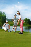 Kids playing golf. By putter on green Stock Image