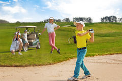 Kids playing golf. By putter on green Stock Photos