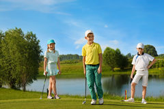Kids playing golf. By putter on green Royalty Free Stock Photo
