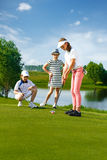 Kids playing golf. By putter on green Stock Photography