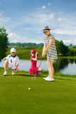 Kids playing golf. By putter on green Stock Images