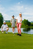 Kids playing golf. By putter on green Stock Photo