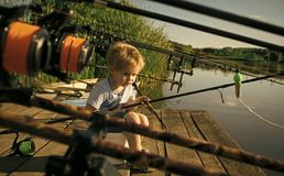 Kids playing - happy game. Adorable little boy fishing from wooden dock on lake. In sunny summer day Stock Photo