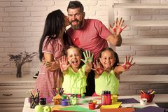 Kids playing - happy game. Happy childhood and parenting. Family love and care concept. Girls drawing with colorful paints. Arts and crafts. Mother and father royalty free stock photo