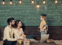 Kids playing - happy game. Homeschooling concept. Smart child in graduate cap likes to study. Parents teaching kid at. Home. Boy presenting his knowledge to mom stock image