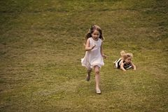 Kids playing - happy game. Kids run and fall on green grass on summer day. On natural landscape. Chase, race, catch, competition concept Stock Image