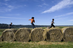Kids playing at hay bales at pumpkin farm Royalty Free Stock Photos