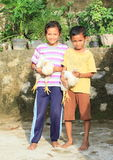 Kids playing with hens. Barefoot kids - girl and boy playing with hens in Labuan Bajo (Flores, Indonesia Stock Image