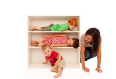 Kids playing hide and seek with mum. Three young kids playing hide and seek on bookshelf with mum looking Stock Image