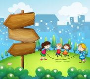 Kids playing in the hills with a wooden signboard Stock Image