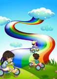Kids playing at the hilltop with a rainbow in the sky Stock Photo