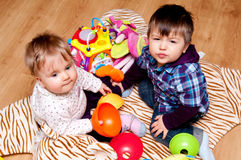 Kids playing at home. Two little toddlers and young girl in the back Royalty Free Stock Photo