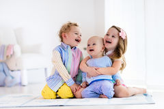 Kids playing at home, brother and sister love. Group of three kids playing in a white bedroom. Children play at home. Preschooler girl, toddler boy and baby in Royalty Free Stock Photo