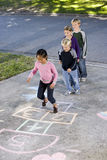 Kids playing hopscotch Stock Photos