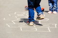 Kids playing hopscotch on playground outdoors Stock Photos