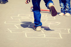 Kids playing hopscotch on playground outdoors Stock Images