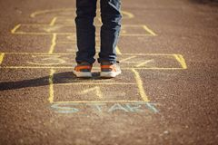 Kids playing hopscotch on playground outdoors. Hopscotch popular street game royalty free stock photo