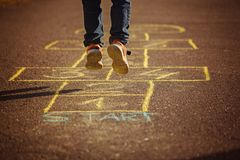 Kids playing hopscotch on playground outdoors. Hopscotch popular street game. Back view Stock Image
