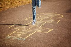 Kids playing hopscotch on playground outdoors. Hopscotch popular street game.  stock image