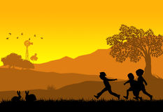 Kids playing. Illustration of a rural landscape background with silhouette of kids playing and rabbits Royalty Free Stock Image