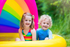 Kids playing in inflatable pool Stock Image
