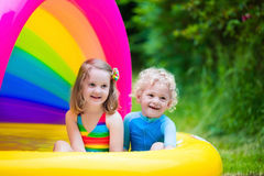 Kids playing in inflatable pool Stock Photography