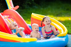 Kids playing in inflatable swimming pool Stock Photo