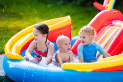 Kids playing in inflatable swimming pool Stock Photography