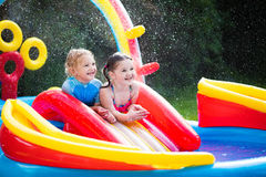 Kids playing in inflatable swimming pool Stock Photos