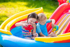 Kids playing in inflatable swimming pool Stock Images