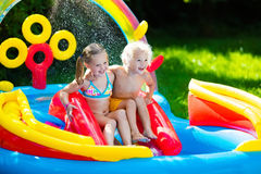 Kids playing in inflatable swimming pool Royalty Free Stock Images