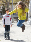 Kids playing in jump rope game Stock Photos