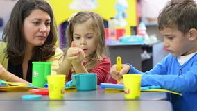 Kids Playing at Kindergarten. Kids playing with plasticine at kindergarten stock video