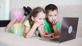 Children are watching a cartoon on a laptop. Kids playing with laptop computer at home. Children are watching a cartoon on a laptop stock footage