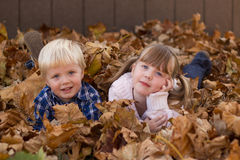 Kids playing in leaf pile leaves Royalty Free Stock Images