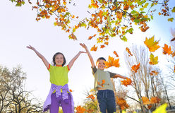 Kids playing with leaves Royalty Free Stock Photos