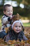 Kids playing with leaves Royalty Free Stock Images