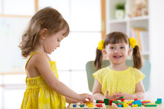 Kids playing with logical toy on desk in nursery room or kindergarten. Children arranging and sorting shapes, colors and sizes. Kids girls playing with logical royalty free stock images