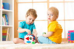 Kids playing with logical toy on soft carpet in nursery roomor kindergarten. Children arranging and sorting shapes or sizes. Royalty Free Stock Images