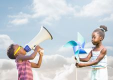 kids playing with megaphone and wind toy with cloudy background royalty free stock photos
