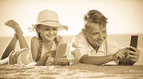 Kids playing with mobile phones Stock Photo