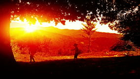 Kids playing, mountain range sunset stock video footage