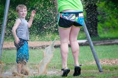 Kids Playing In Mud. A boy kicking up some muddy water at a girl walking by Royalty Free Stock Images