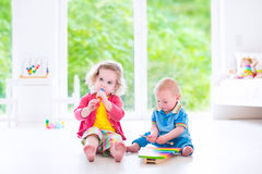 Kids playing music with xylophone. Two little children - cute curly toddler girl and a funny baby boy, brother and sister playing music, having fun with colorful royalty free stock images